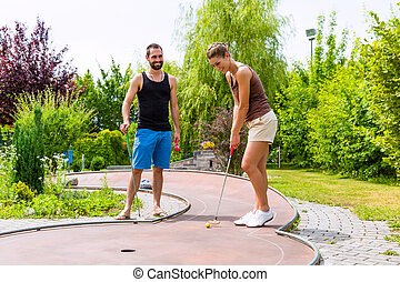 Couple playing together miniature golf outdoors
