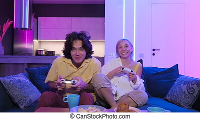Couple playing videogame on console. Girl losing and not letting the guy play normally by closing his eyes with her hand. Having fun together at home on quarantine.