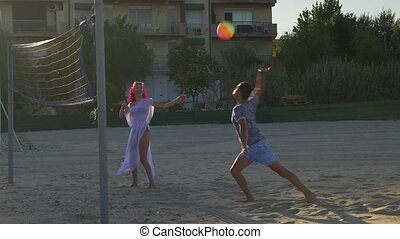 Couple playing volleyball and having fun on the beach
