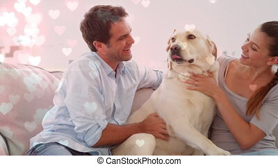 Couple playing with a dog on the couch against illustration of hearts