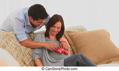 Couple playing with baby shoes on t