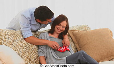 Couple playing with baby shoes