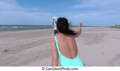 Couple playing with Frisbee disc on the beach