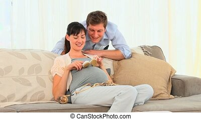 Couple playing with shoes of their future baby on a sofa