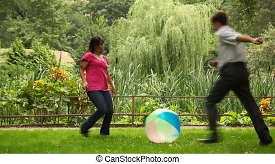 couple plays with ball near fence in park