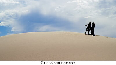 Couple pointing at a distance in desert 4k