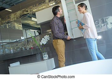couple pointing at ceramic mosaic tile in store