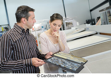 couple pointing at ceramic tile for bathroom floor in store