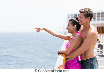 couple pointing at ocean