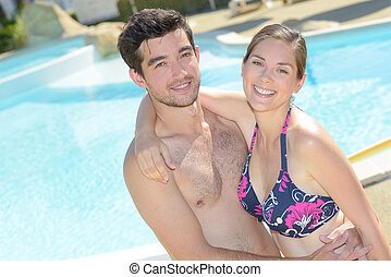 Couple posing by swimming pool