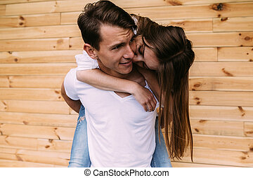 couple posing on a background of the wooden wall