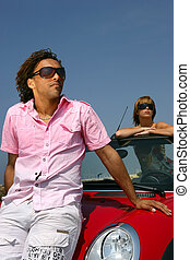 Couple posing with their car