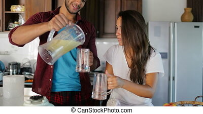 Couple Pour Fresh Juice From Blender In Glasses Man And Woman In Kitchen Talking Together Happy Smiling