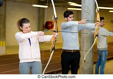 couple practicing archery indoors