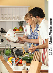 Couple preparing a meal with the help of a cookbook