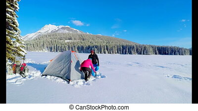 Couple preparing a tent on snowy landscape 4k - Couple...