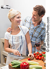 Couple preparing food together in k