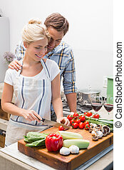 Couple preparing food together in the kitchen - Young couple...