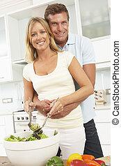 Couple Preparing Salad In Modern Kitchen