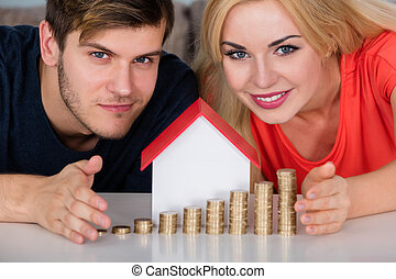 Couple Protecting House Model With Stacked Coins