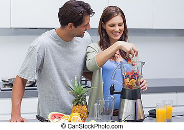 Couple putting fruits into blender - Couple putting various...