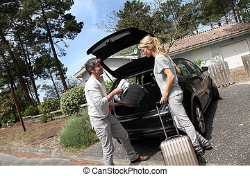 Couple putting suitcases in car trunk for a journey