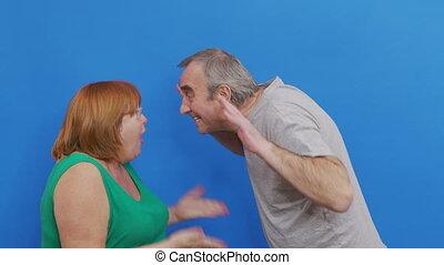 Couple quarreling on blue background. Aged couple quarreling. Conflict, negative emotions