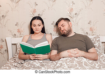 Couple reading a book in bed.