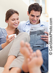 Couple reading a newspaper while lying on a couch