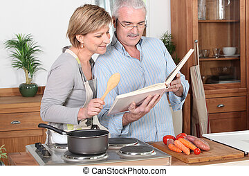 Couple reading a recipe book