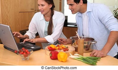 Couple reading a recipe on a laptop to cook in the kitchen