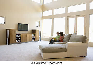 Couple reading book in living room smiling