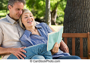 Couple reading book on park bench