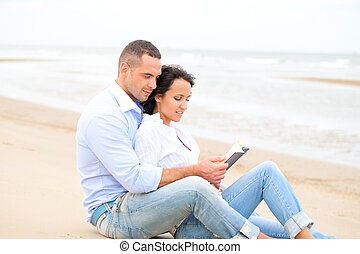 Couple reading book on the beach