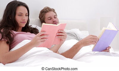 Couple reading books in bed