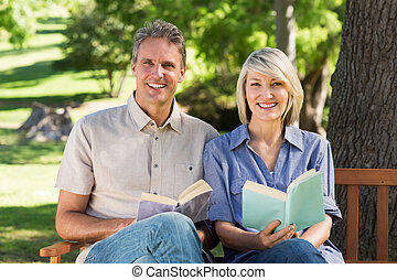 Couple reading books on bench in park