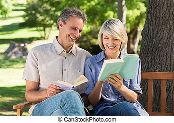 Couple reading books on bench