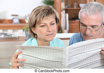 Couple reading newspaper in kitchen