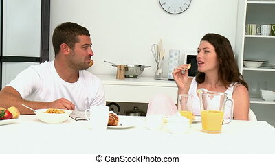 Couple reading newspaper while they having breakfast