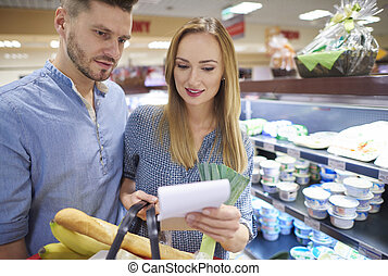 Couple reading shopping list in supermarket
