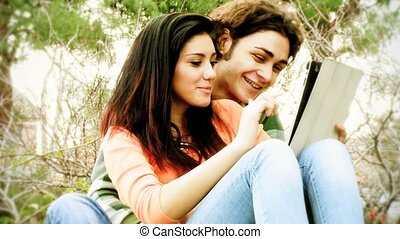 Couple reading tablet happy