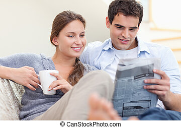 Couple reading the news while lying on a sofa