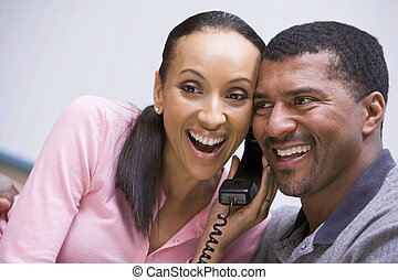 Couple receiving good news over phone at home