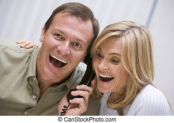 Couple receiving good news over the phone at home