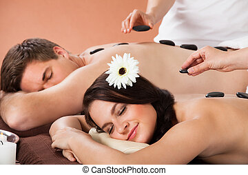 Couple Receiving hot stone Therapy At Spa - Relaxed young...