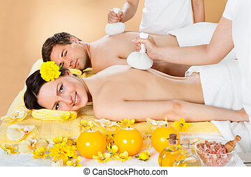 Couple Receiving Massage With Herbal Compress Stamps At Spa...