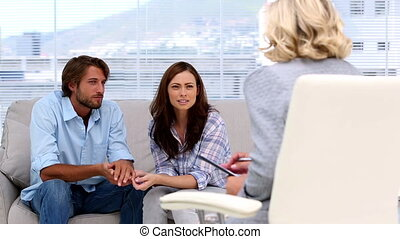 Couple reconciling thanks to their woman therapist