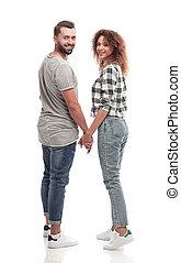 couple, regarder, appareil photo, tenant mains, heureux, vue postérieure