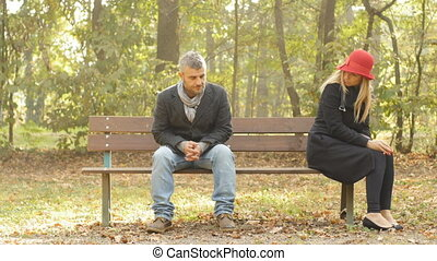 adult caucasian elegant couple having relationship problems sitting outdoor on a bench, they are sad and don't talk each other