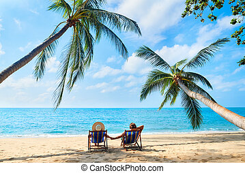 Couple relax on the beach enjoying beautiful sea on the tropical island